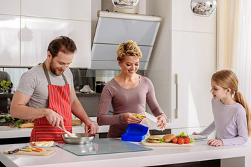 Friendly family cooking together in kitchen