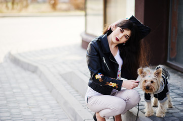Brunette gypsy girl with yorkshire terrier dog posed against large windows house. Model wear on leather jacket and t-shirt with ornament, pants and shoes with high heels.