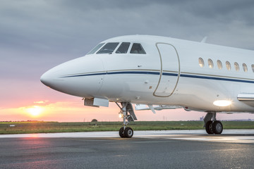 Large private business jet on runway, ready for takeoff, during sunrise