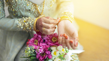 graceful poses of girls hand wearing gold bangles, with beatiful flower, selective focus shallow DOF.