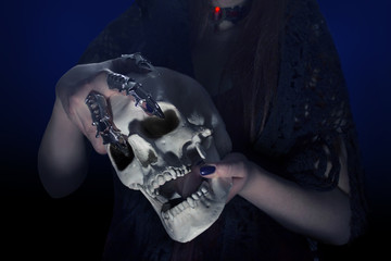 A woman's hands with steel fingertips on holding a human skull photo.