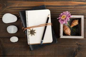 Open blank notebook, pebbles, shells, flower