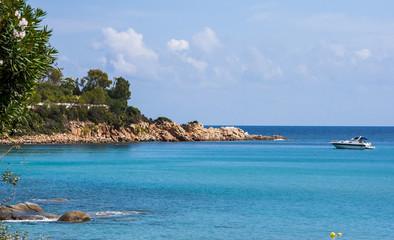 Scenery view Italian island Sardinia sea shore beach rock coast and anchored boat in Arbatax sardegna