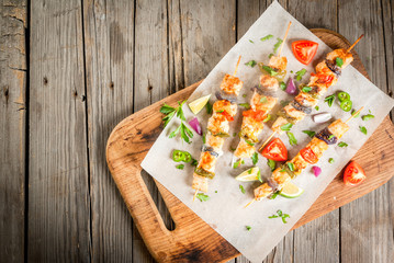 Fajita chicken kebabs, with chicken meat, pepper, chili, tomatoes, onions, lime juice and herbs. In a frying pan, on a rustic wooden table. Mexican cuisine, a traditional food,