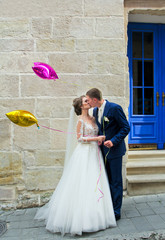 Gorgeous wedding couple kissing and keeps colorful balloons. Bride and groom standing near stones wall and blue door