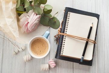 Open blank notebook, bouquet, cup of coffee, earphones