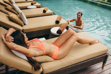 Man in pool with woman on deckchair at poolside Wall mural