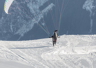 The pilot begins flight on a paraplane with a mountain-skiing slope of Penken - Mayrhofen, Austria