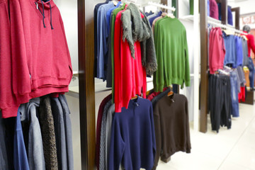 Racks with different clothes in modern shop