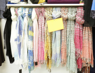 Rack with different scarfs in modern shop