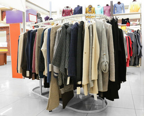 Rack with different clothes in modern shop