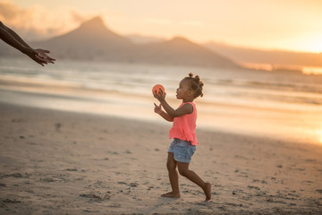Little girl holding ball at the beach at sunset