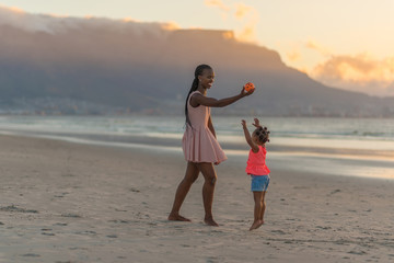 Mother playing with her daughter at the beach