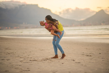 Mother playing with little girl at the beach