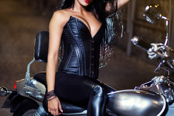 Close-up shot of gothic woman in leather corset,Close-up shot of woman wearing professional waist training black leather corset,A girl in a leather corset sits on a bike