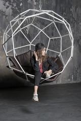 pretty woman in cap in geometric chair