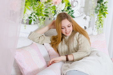 Beautiful young woman resting on a bed decorated with flowers