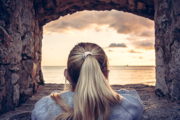 Thoughtful woman devoted into contemplation of beautiful sunset over sea through window of old castle with dramatic sky and perspective view. View from behind. Concept for forecasting and way forward Wall mural