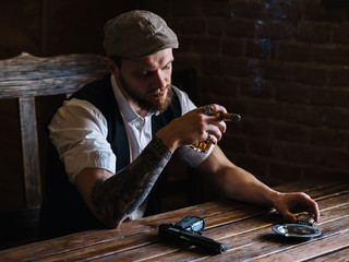 A young bearded man smoking a cigar in a pub