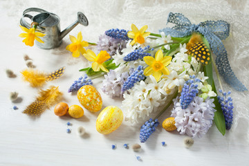 Easter spring flowers hyacinths, daffodils and eggs on a wooden table