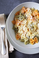 Multicolored farfalle pasta with grated cheese