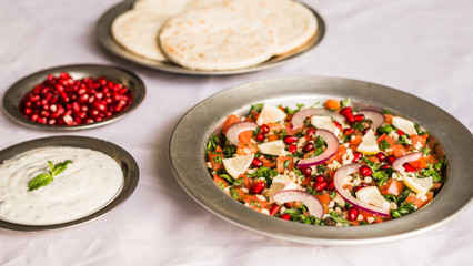 Tabbouleh salad and Arab pita bread with pomegranate seeds and white sour cream sauce against white background. Selective focus.