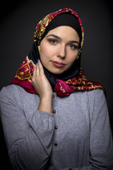 Fashion model wearing hijab for conservative modern clothing mostly associated with muslims, middle eastern and east european culture.  The outfit depicts the traditional headscarf in vogue style.
