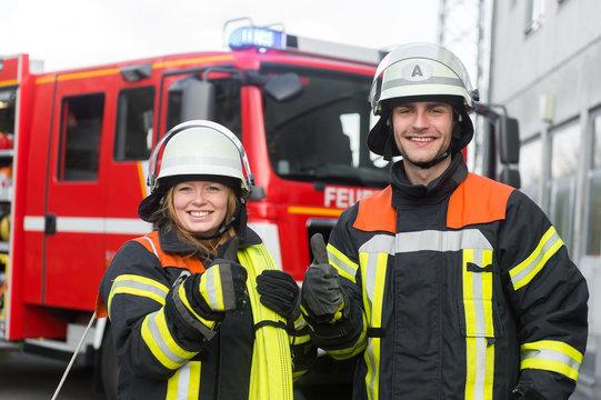 Feuerwehrmann und Feuerwehrfrau strecken den Daumen in die Kamera