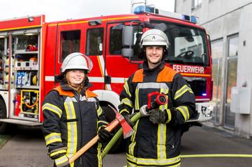Feuerwehrmann und Feuerwehrfrau an einer Einsatzstelle