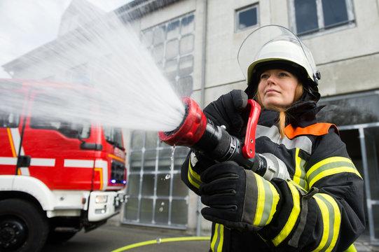 Junge Feuerwehrfrau löscht ein Feuer