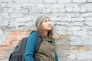 Young woman with backpack in casual style leaning against urban brick wall looking up