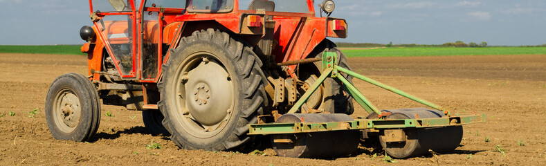 Tractor standing on agricultural field during spring sowing