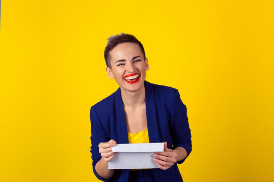 Happy woman smiling holding envelope letter isolated yellow background wall. Positive face expression human emotion body language