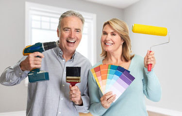 Senior couple with drill and painting roller
