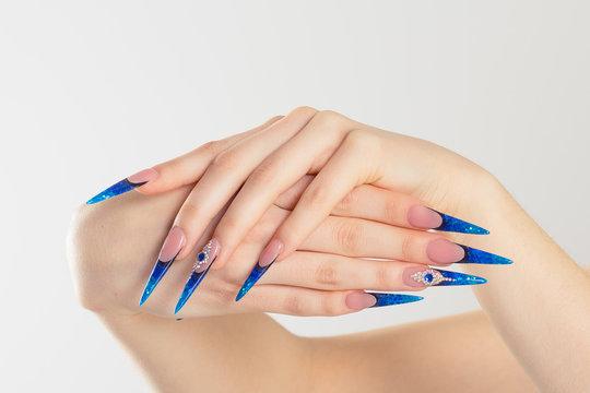 Nail Polish. Art Manicure. Modern style blue Nail Polish. Cropped horizontal image Beauty hands with Stylish Colorful stiletto blue Nails isolated white background