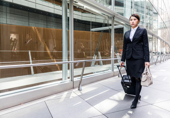 business woman walking by pulling a suitcase near a building