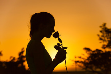Silhouette of woman smelling a rose flower.