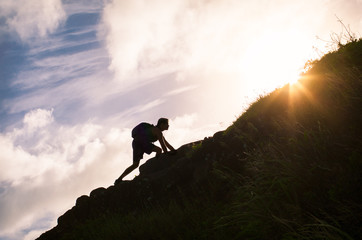 Young man climbing up a mountain. Self improvement and life goals concept.