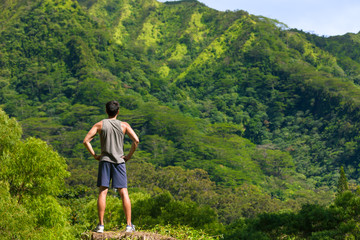 Fit active lifestyle. Young man standing against a green mountain view. (location Hawaii)
