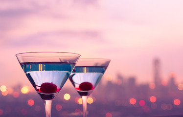 Martini drinks on a bar against city lights. City night life  and party concept.