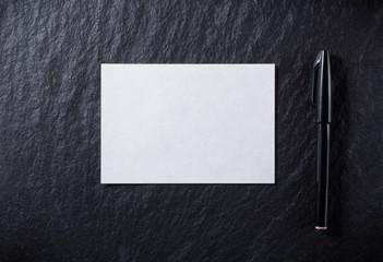 黒背景に白い紙と黒いペン