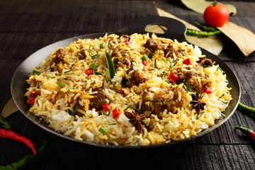 Overhead view=-Homemade delicious mutton dum biriyani or pilaf served in cast iron cookware.