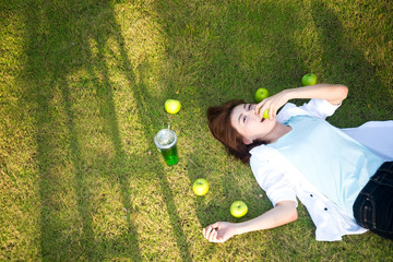 Young women lying in summer grass with eat apple relaxing, sunny day, greenery tone 2017..