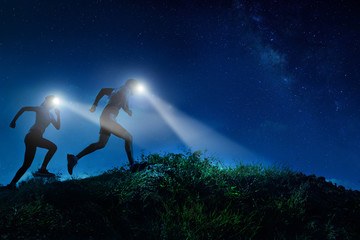 Night trail runner of men and women running on the mountain.at night milky way