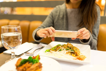 Woman taking photo on her dinner