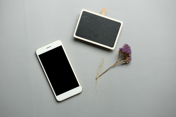 Creative flat lay photo of workspace desk with smartphone , black sign , dry flower on gray wood background