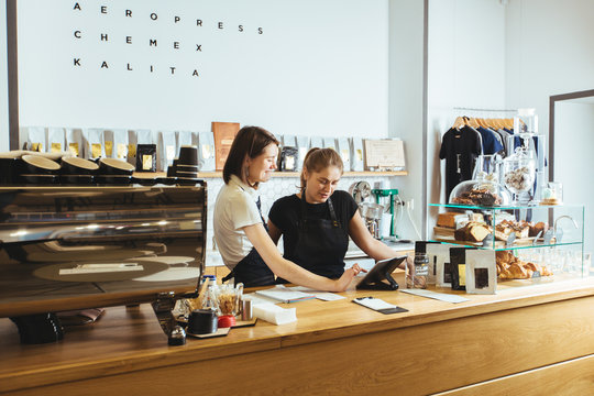 Two female barista working with  tablet behind the counter in the  coffee shop. Coffee culture concepts with real people models.