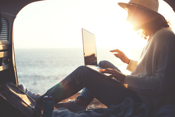 Young traveling female sitting in the trunk of van and enjoing the adventure, woman hipster using computer in the car at sunset