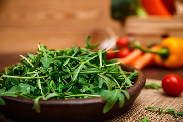 Arugula leaves in bowl. Fresh salad. Pepper and cherry tomato. Natural raw vegetables. Organic bio food on rustic wooden table.