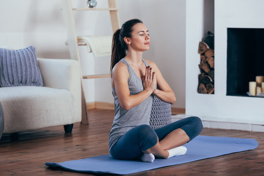 attractive young woman sitting on lotus position on floor with eyes closed.
